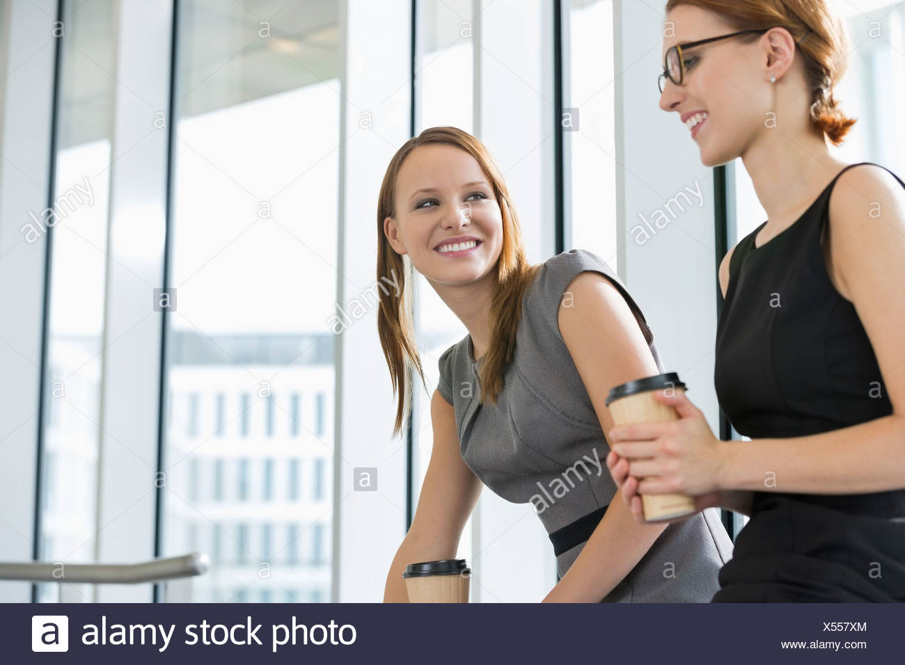 Businesswomen with disposable coffee cups at office - Stock Image