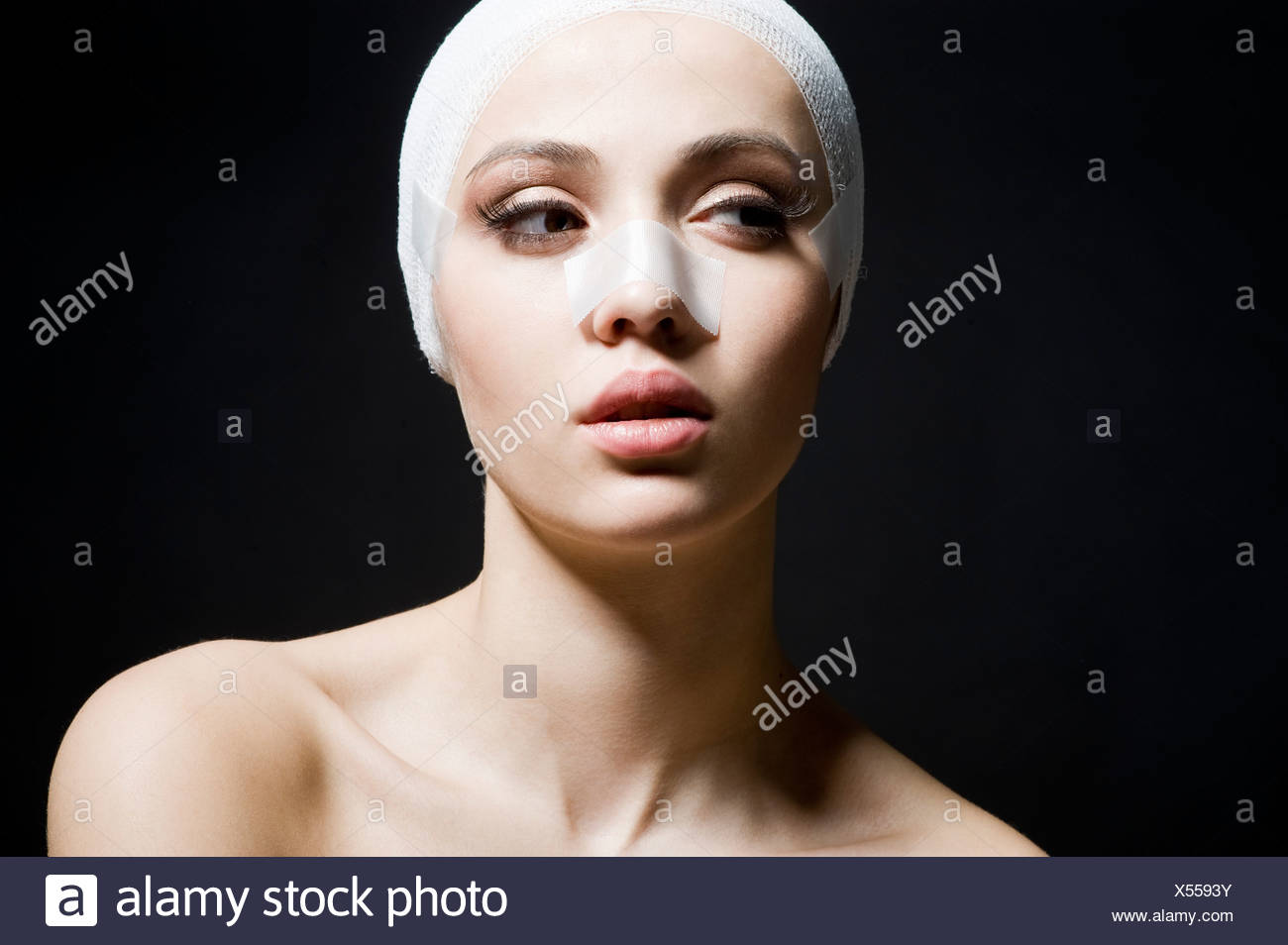 young woman with plaster on face Stock Photo