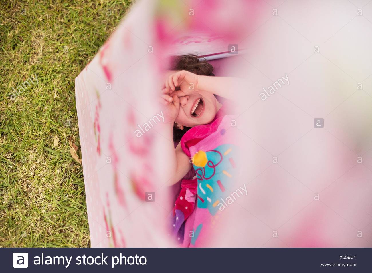Overhead view of girl in teepee, hands covering eyes smiling - Stock Image