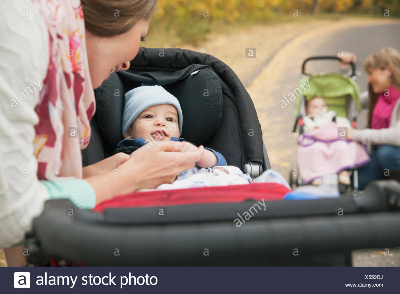 Happy mothers playing with babies in carriages - Stock Image