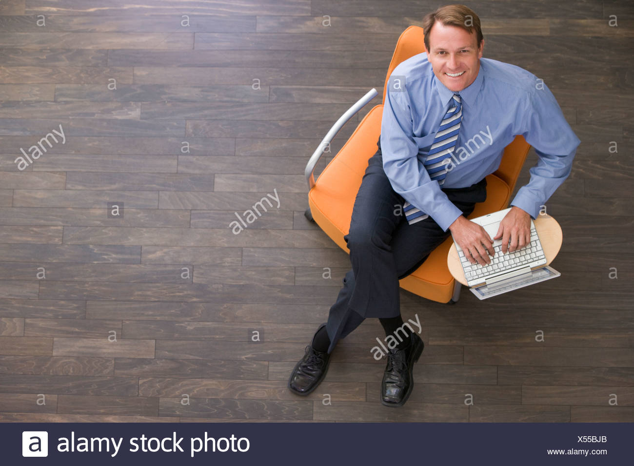 Businessman sitting indoors with laptop smiling - Stock Image