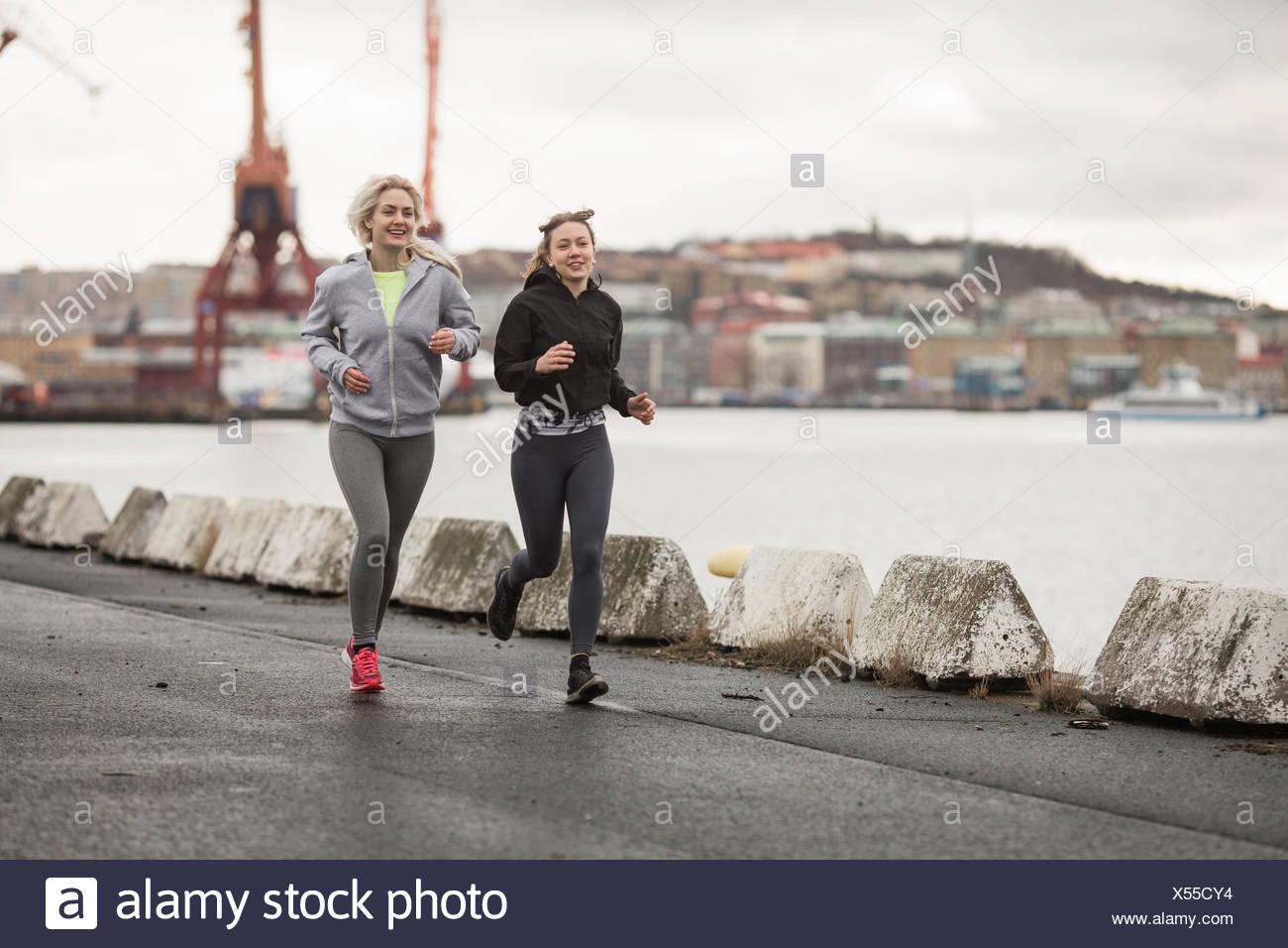 Two female runner friends running along dockside - Stock Image