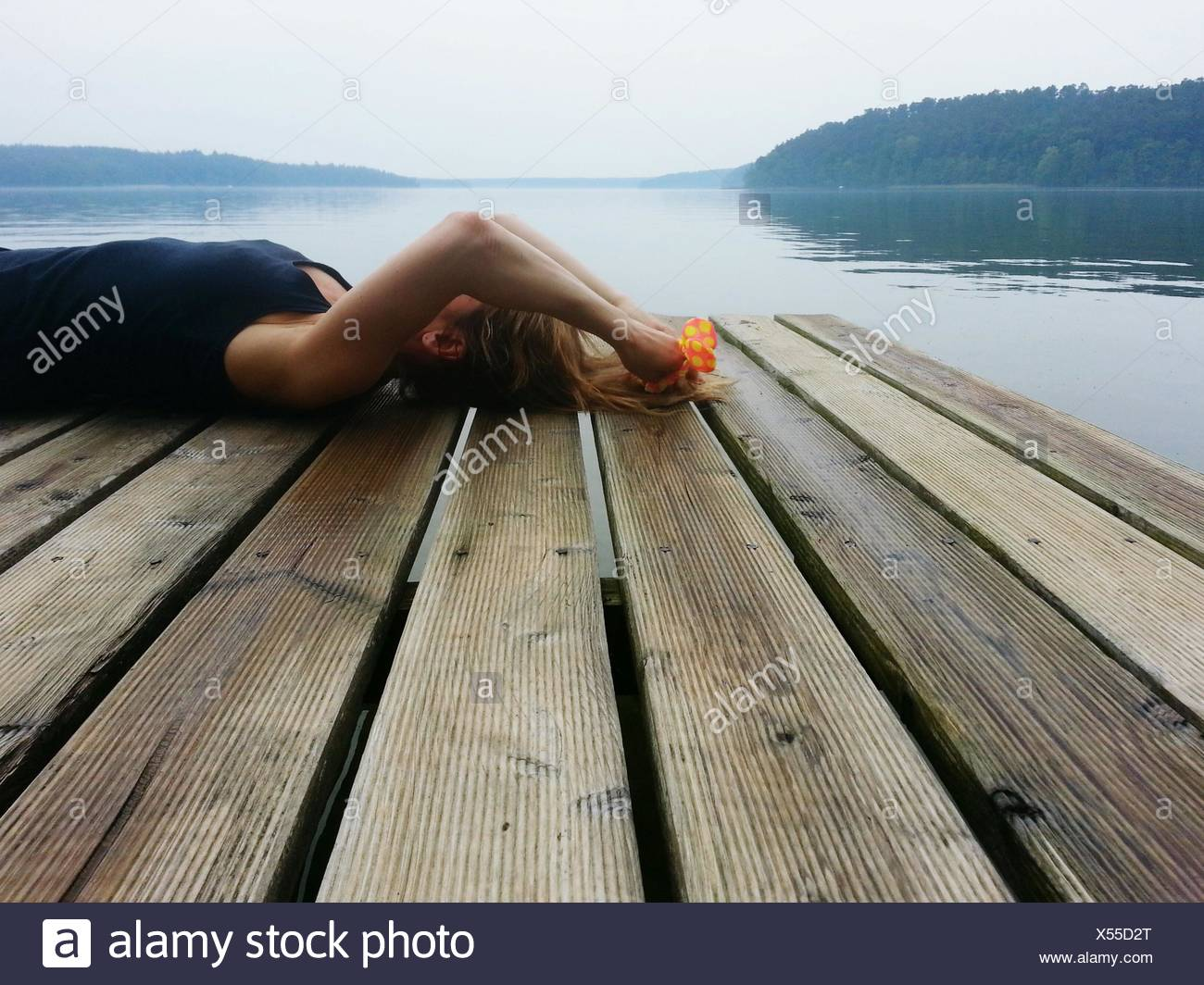 Woman Lying On Wooden Pier In Front Of River Against Sky - Stock Image
