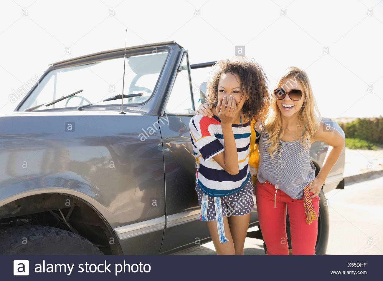 Cheerful female friends standing by off-road vehicle - Stock Image