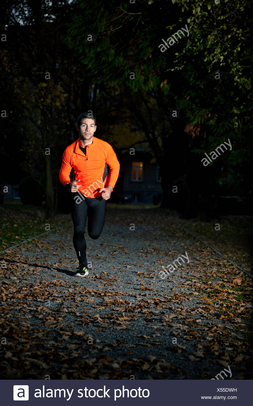 Male runner doing sprint training at twilight - Stock Image