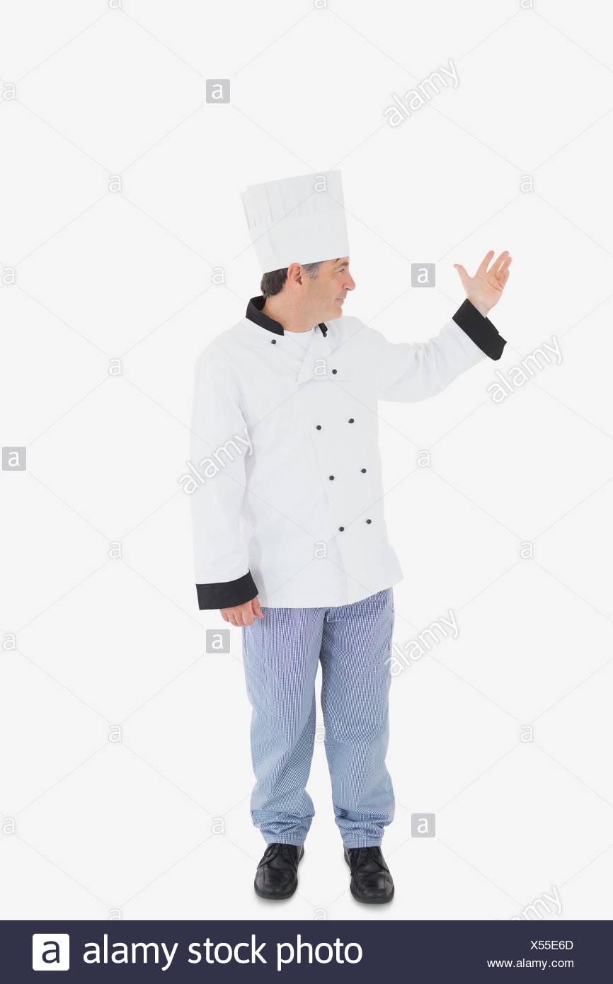 Confident chef showing something on white - Stock Image