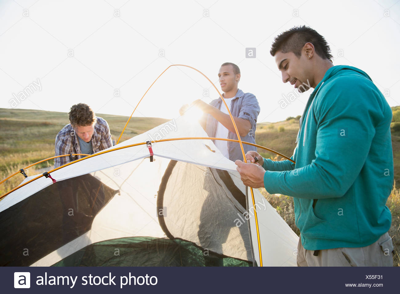 Friends inserting poles into tent for camping. - Stock Image