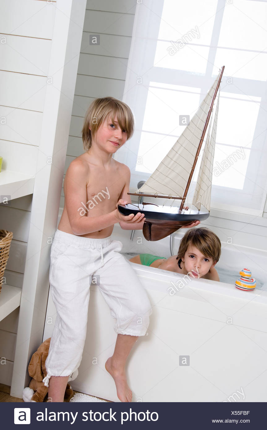 2 boys in bathroom, one having a bath, the other holding a model ...