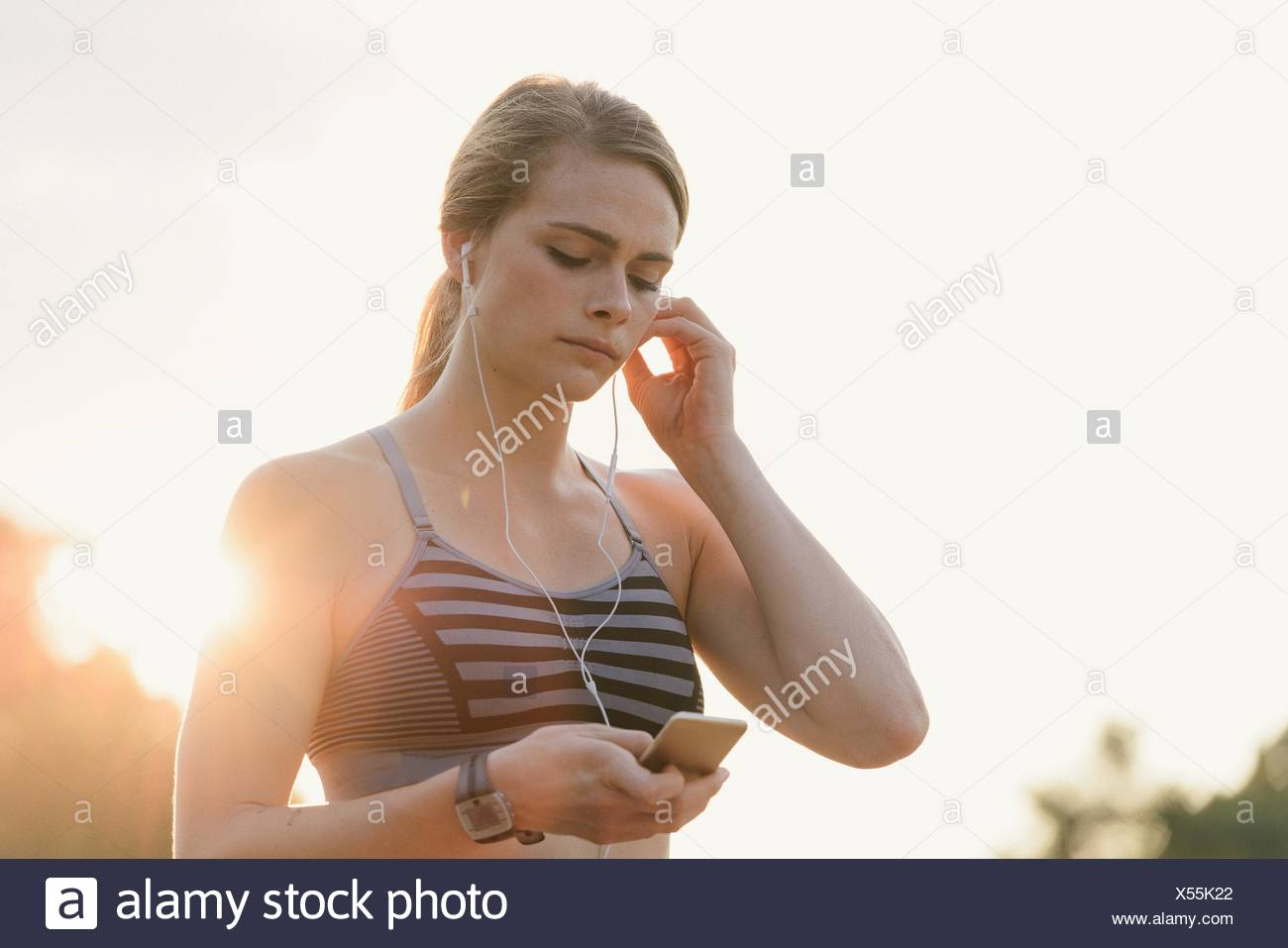Young woman working out, wearing earphones, holding mp3 player - Stock Image