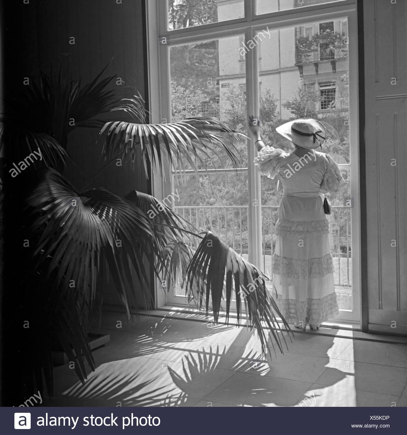 Eine ältere Dame in einem bodenlangen Kleid steht an einem Fenster eines Palmengartens, Deutschland 1930er Jahre. An elder lady in a long dress standing in front of a high window of a palm tree garden, Germany 1930s. Stock Photo