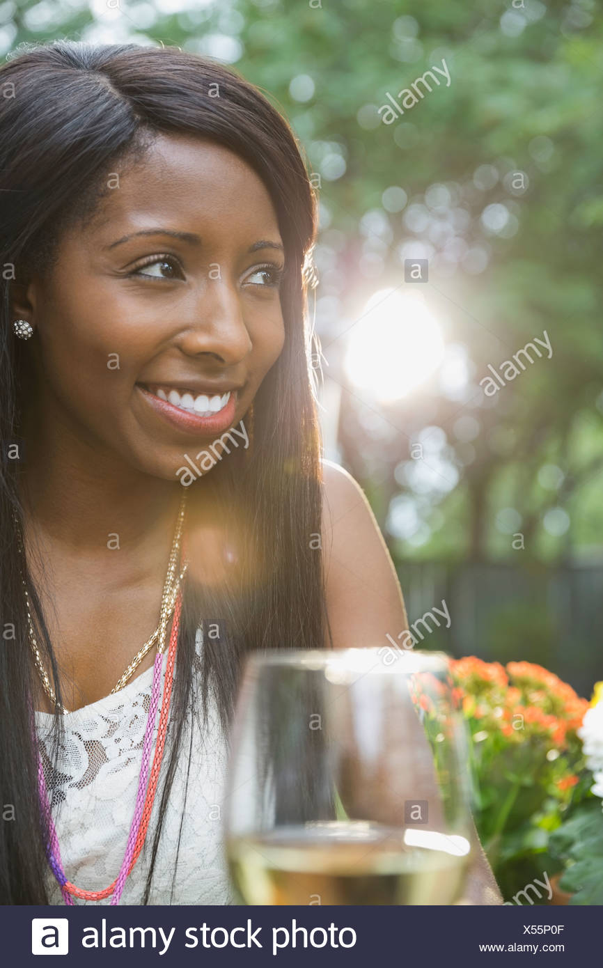 Smiling woman with wineglass sitting in yard - Stock Image