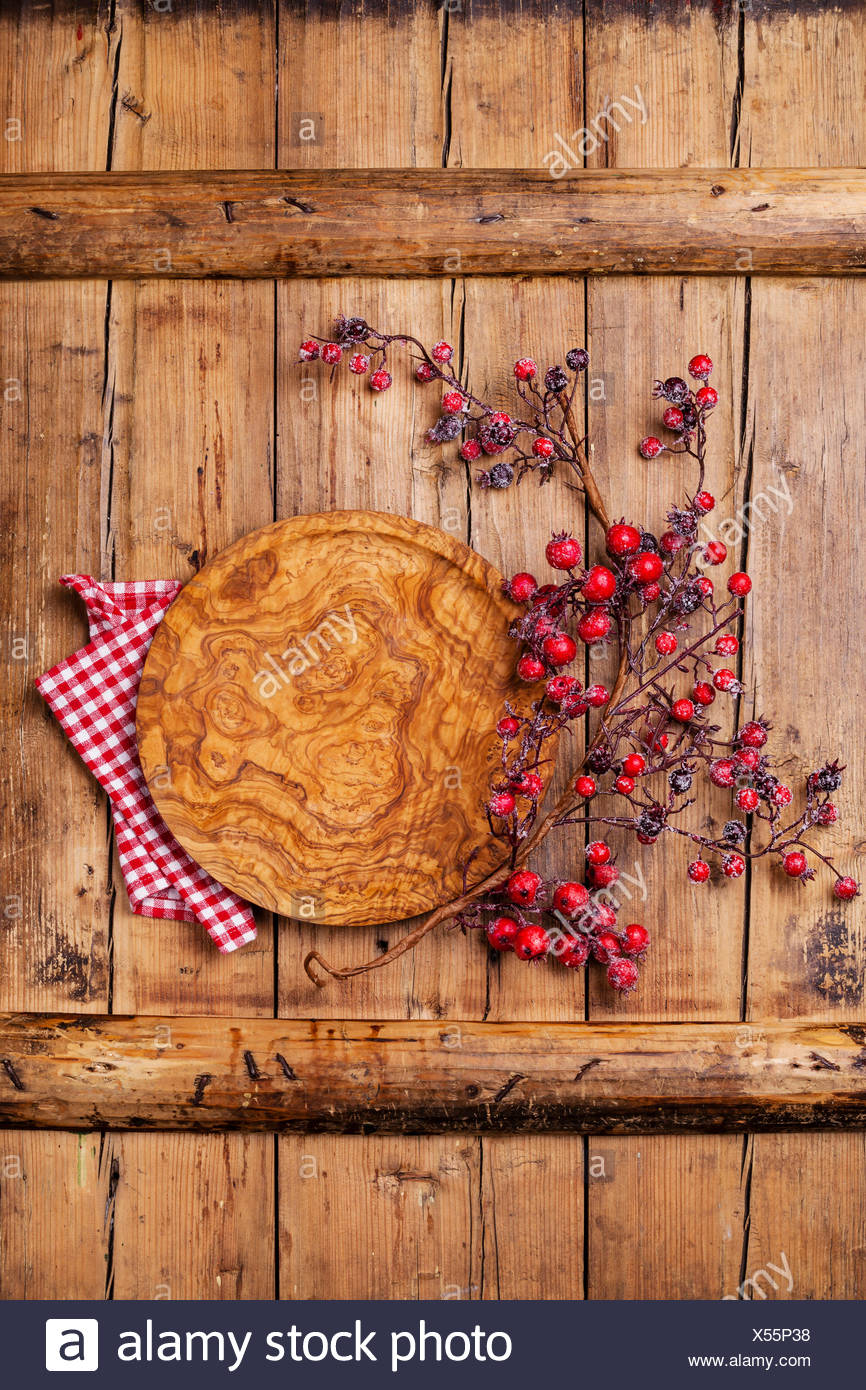 Plate round and branch with red berries on wooden texture background - Stock Image