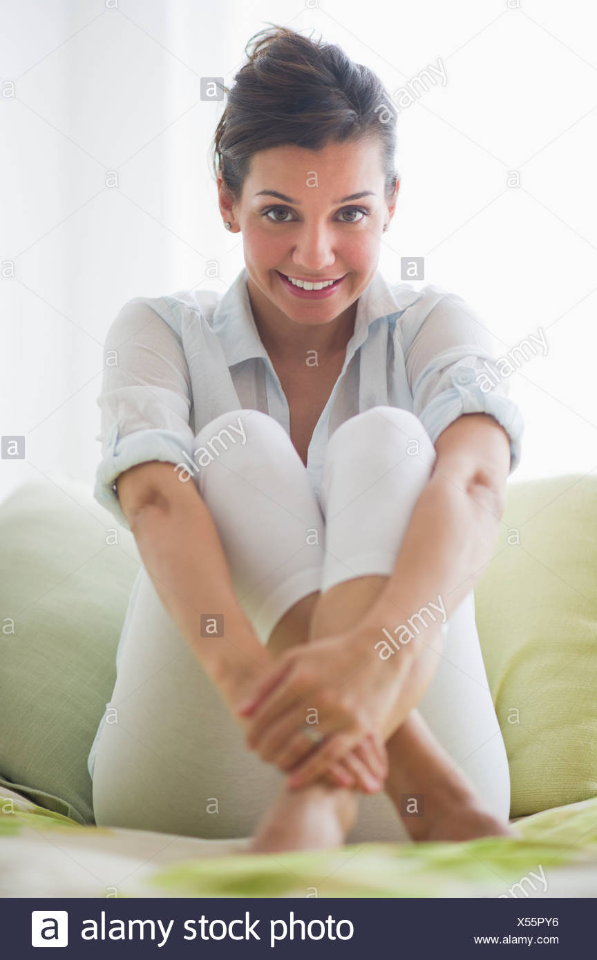 Portrait of cheerful young woman sitting with legs crossed - Stock Image