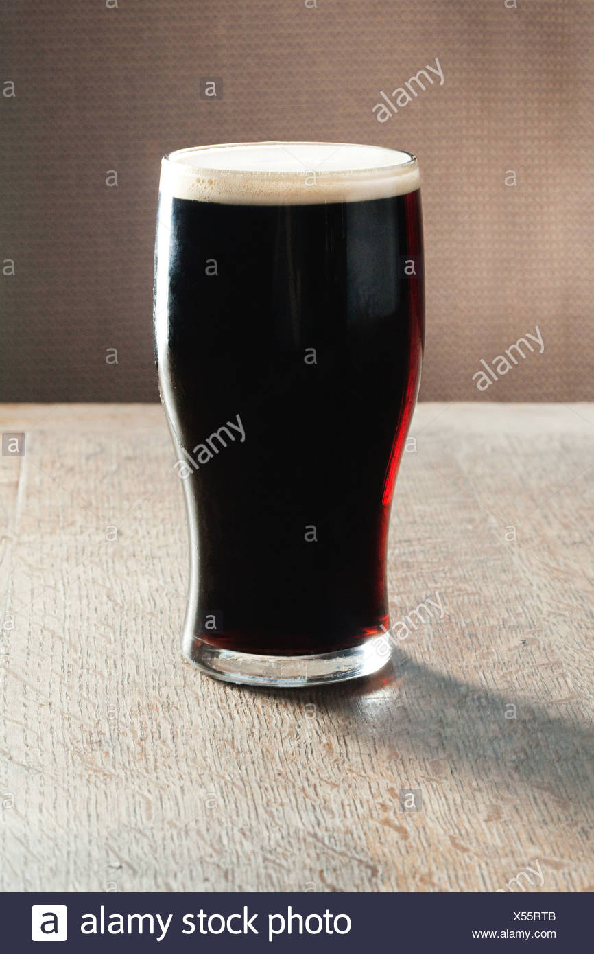 Pint of beer on table - Stock Image