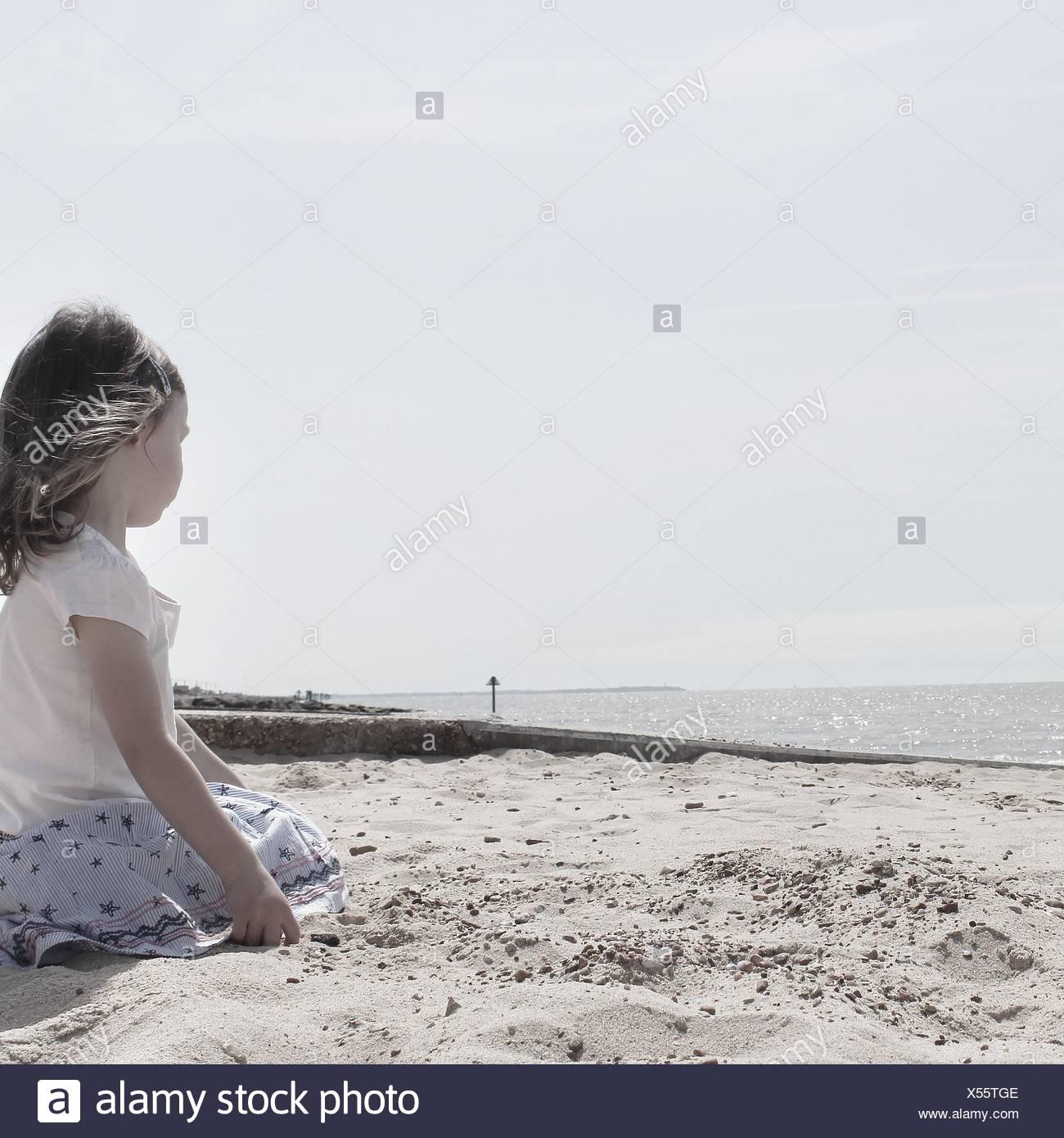 Girl sitting on the beach - Stock Image