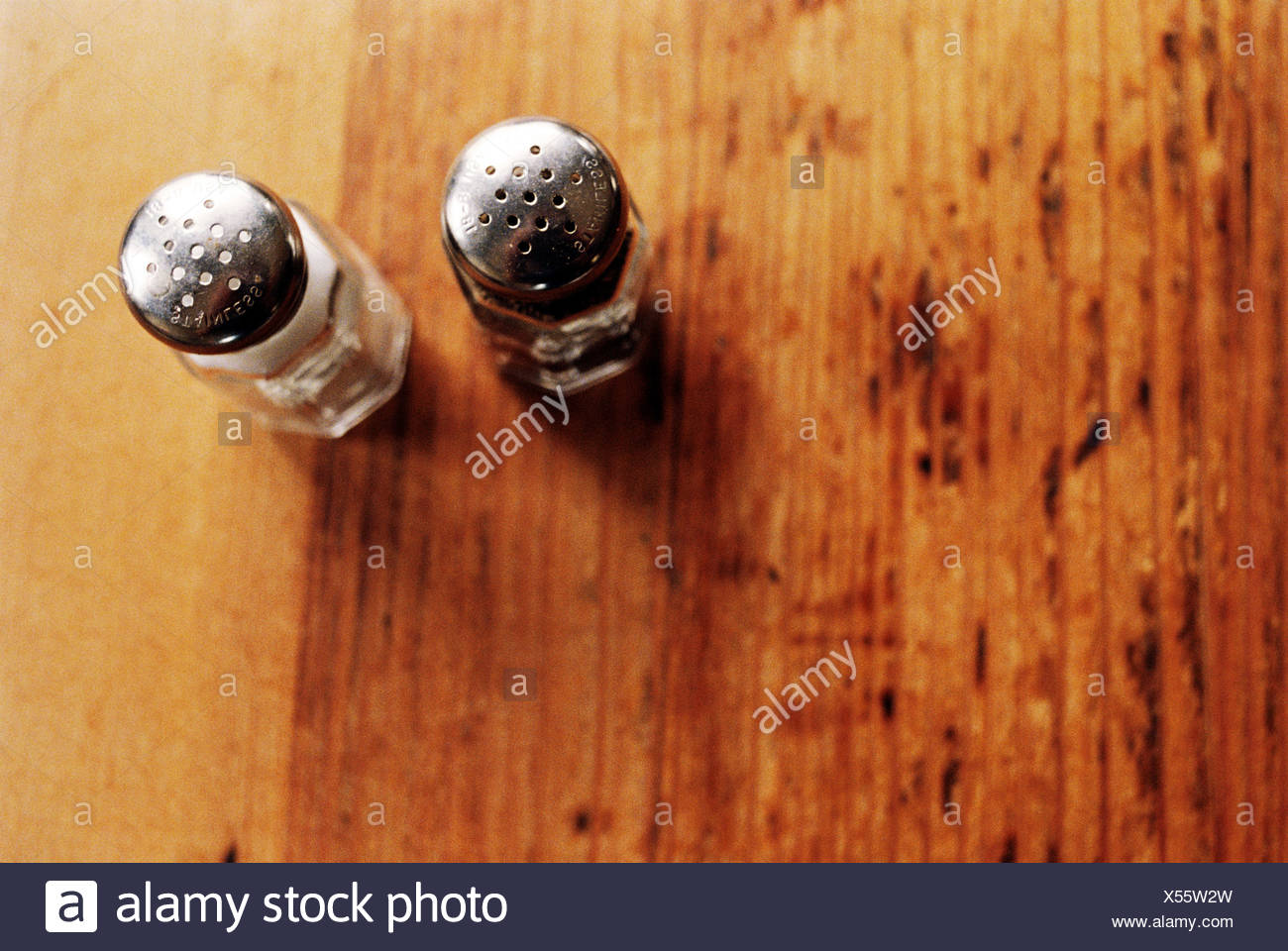 Salt and pepper pots on wooden table Stock Photo