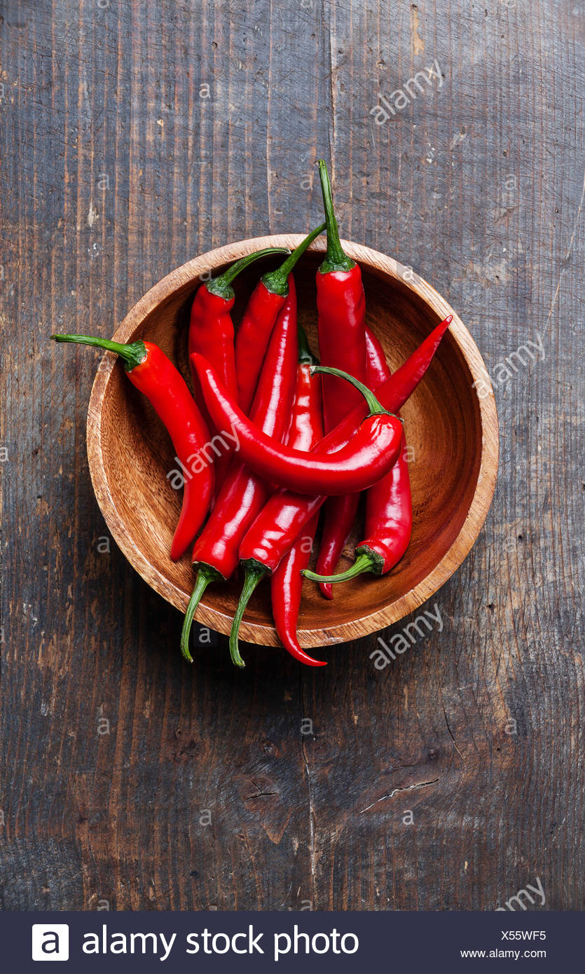 Red Hot Chili Peppers in wooden bowl on old wooden background - Stock Image