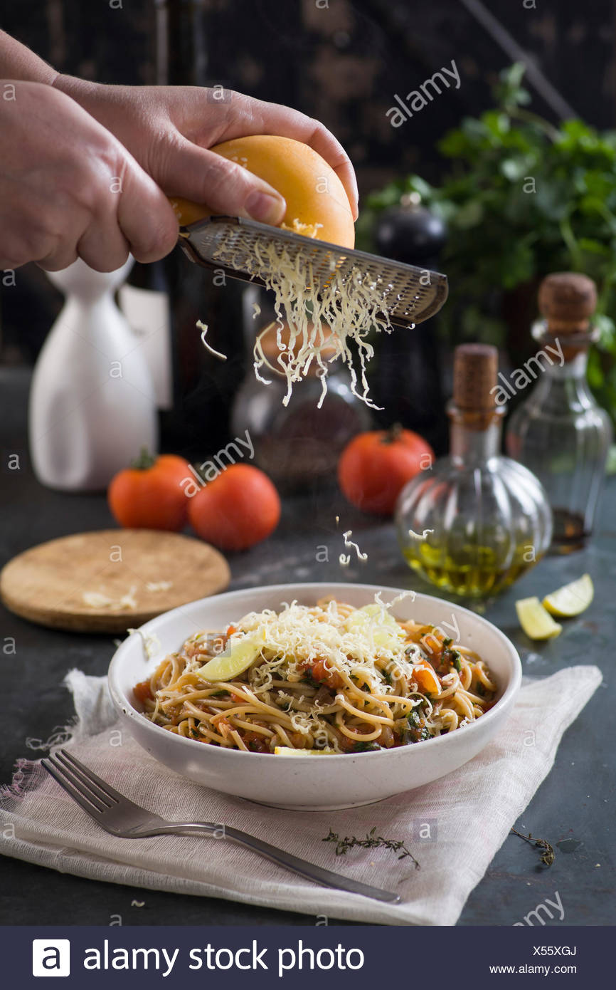 cheese grated over spaghetti with tomato sauce and herbs - Stock Image