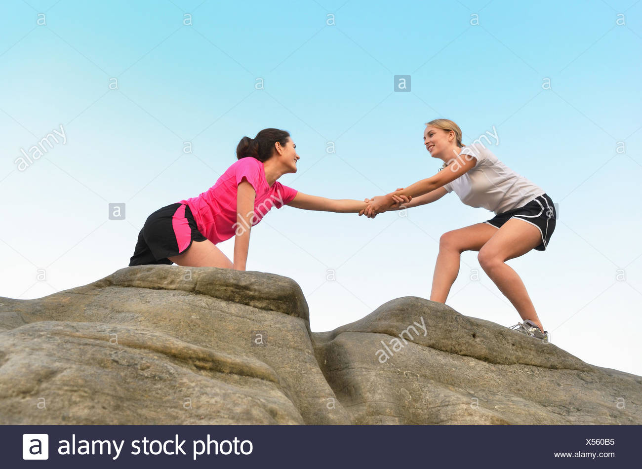 Young female runner helping friend to top of rock formation - Stock Image