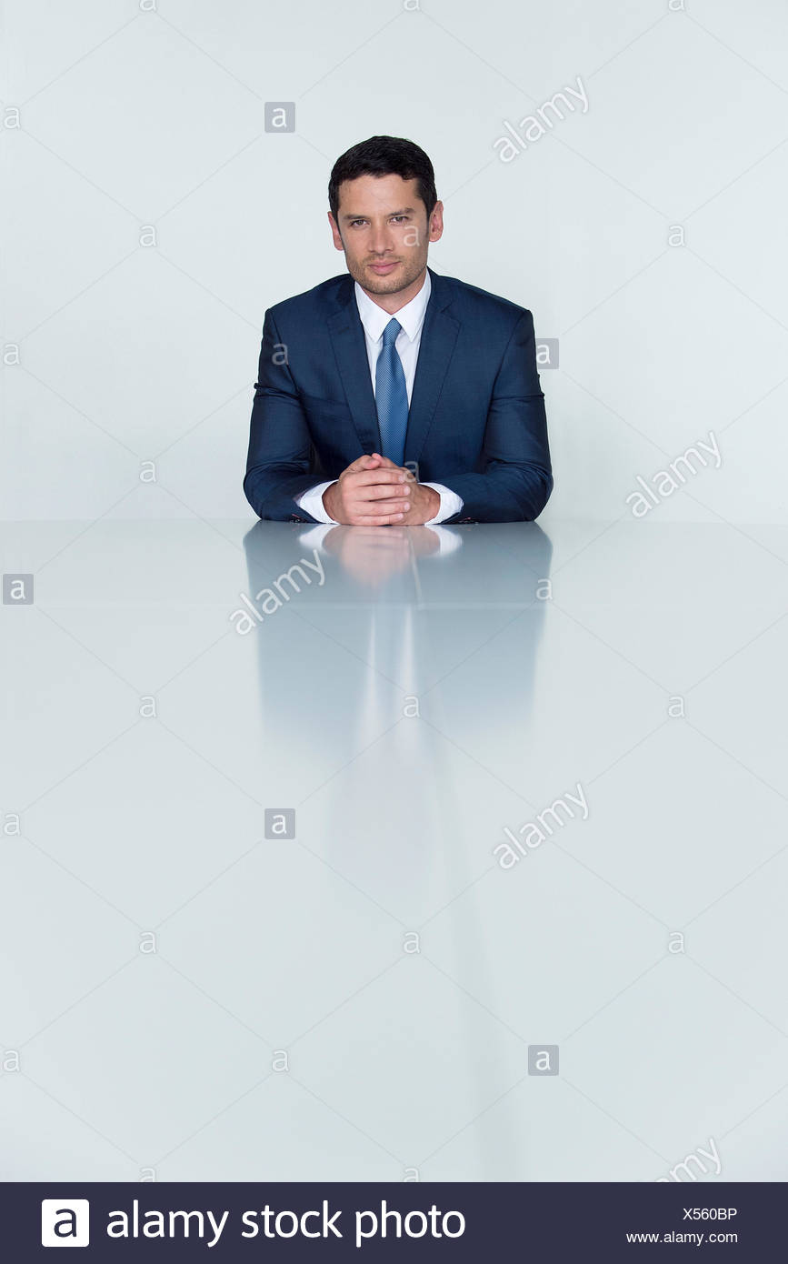 Businessman seated at table, portrait - Stock Image