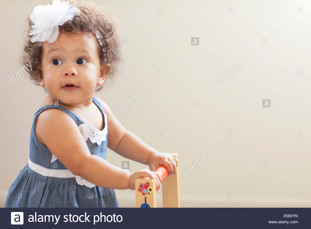 Portrait of baby girl, pushing baby walker - Stock Image