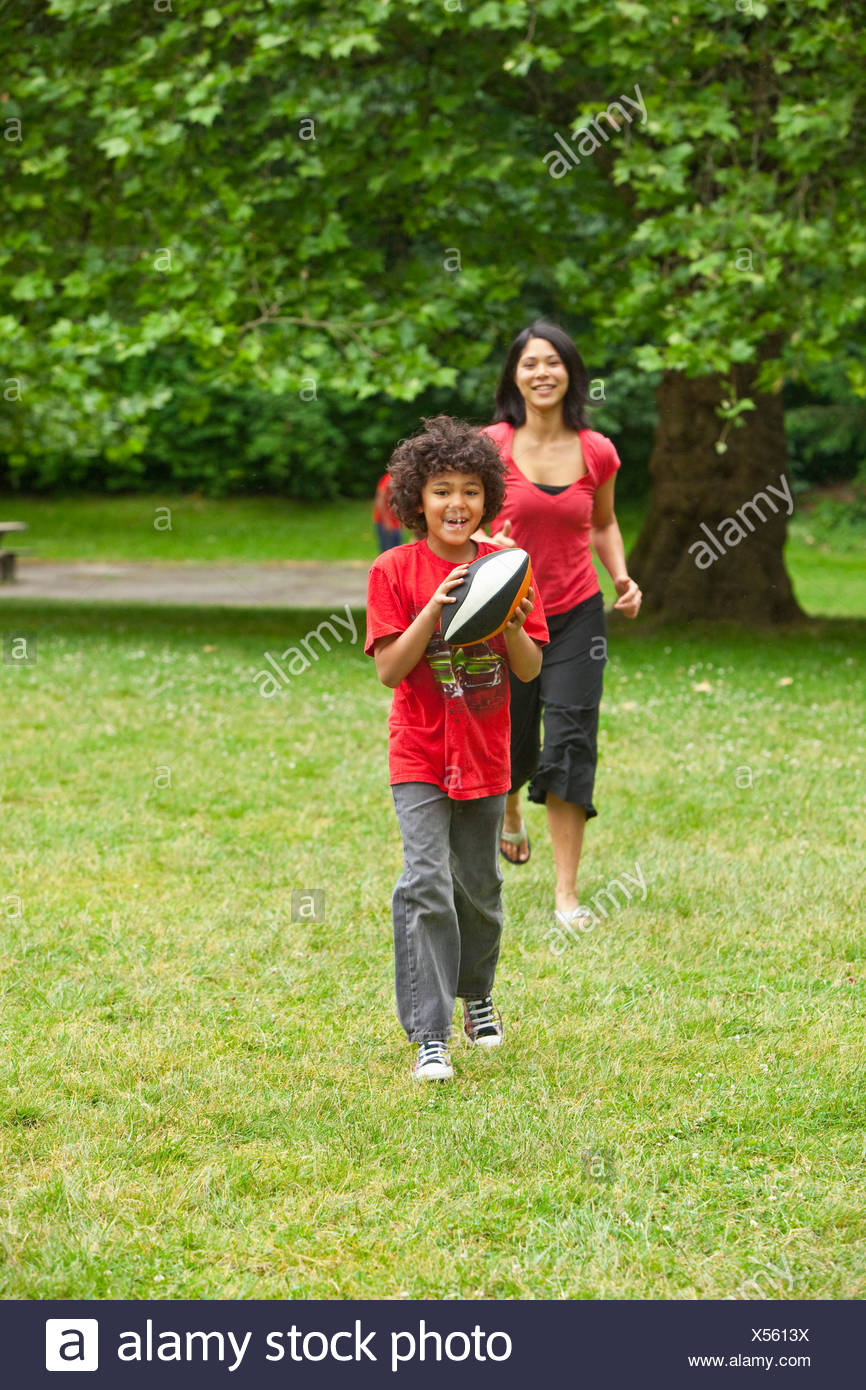 Boy with football running from mother - Stock Image