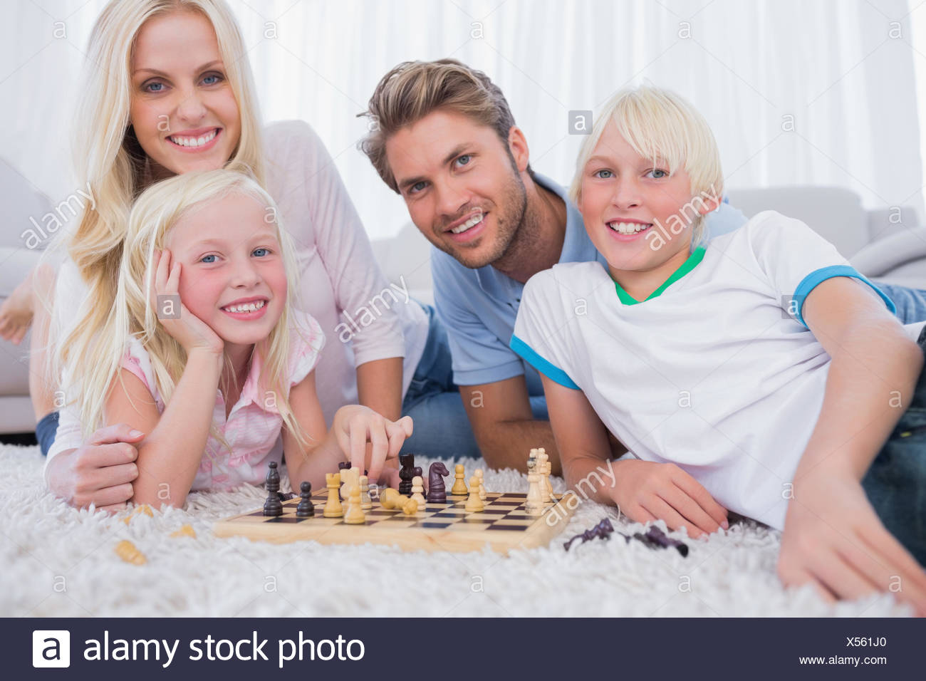 Smiling family playing chess together - Stock Image