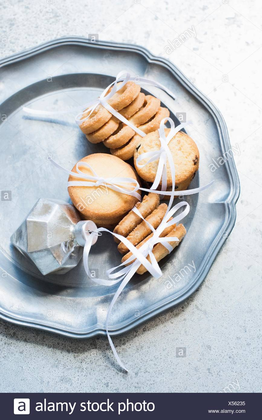 Overhead view of shortbread cookies tied with white ribbon on silver serving dish - Stock Image