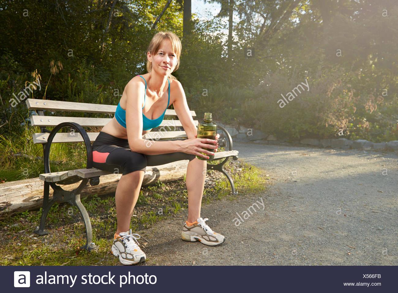 Portrait of smiling female runner taking a break on park bench - Stock Image