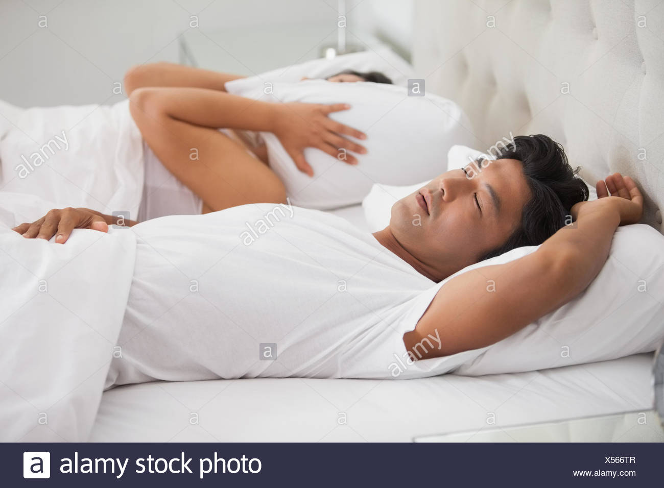 Woman covering her ears as partner is snoring loudly - Stock Image