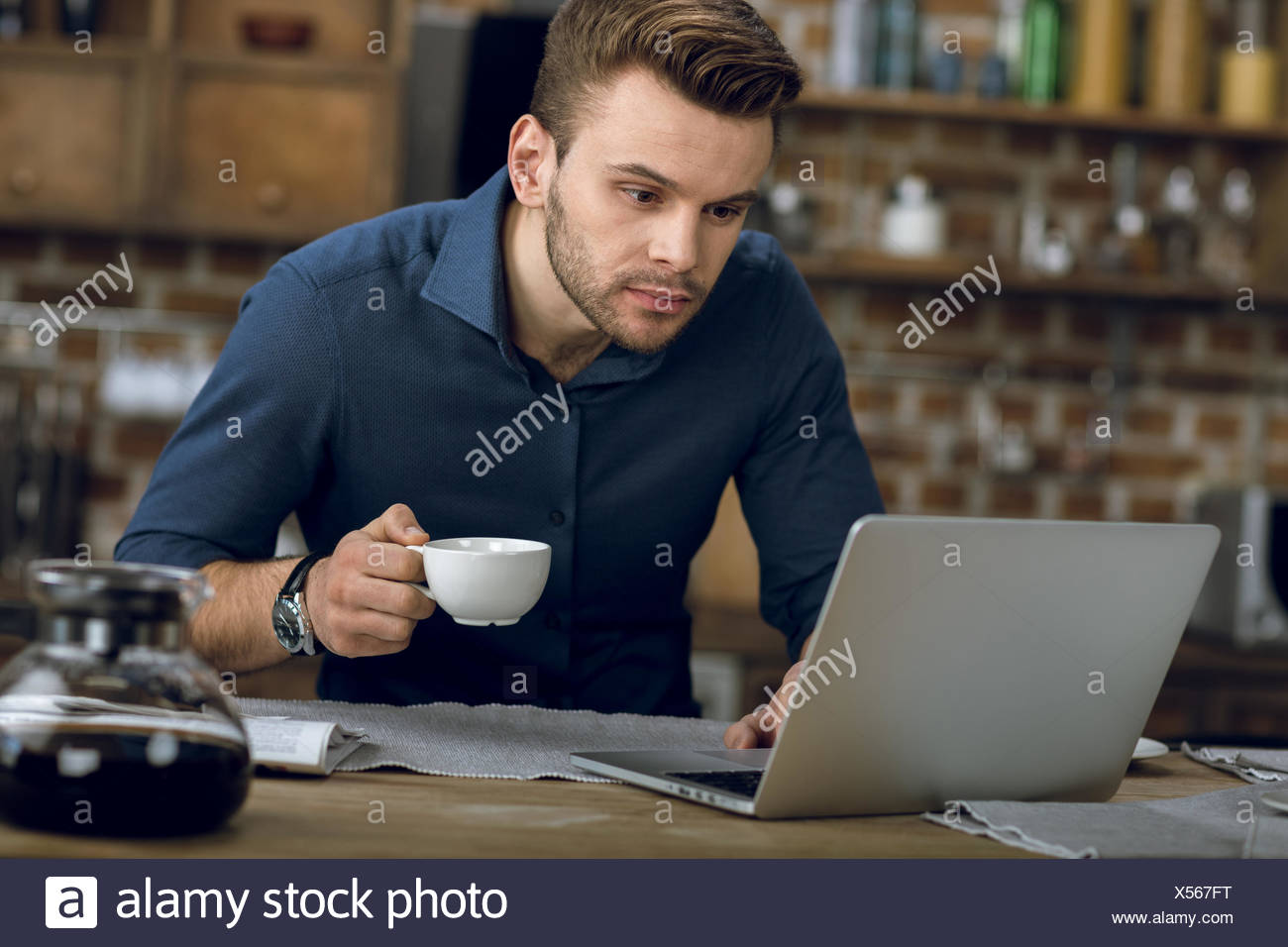 Concentrated young man using laptop while drinking coffee at home - Stock Image