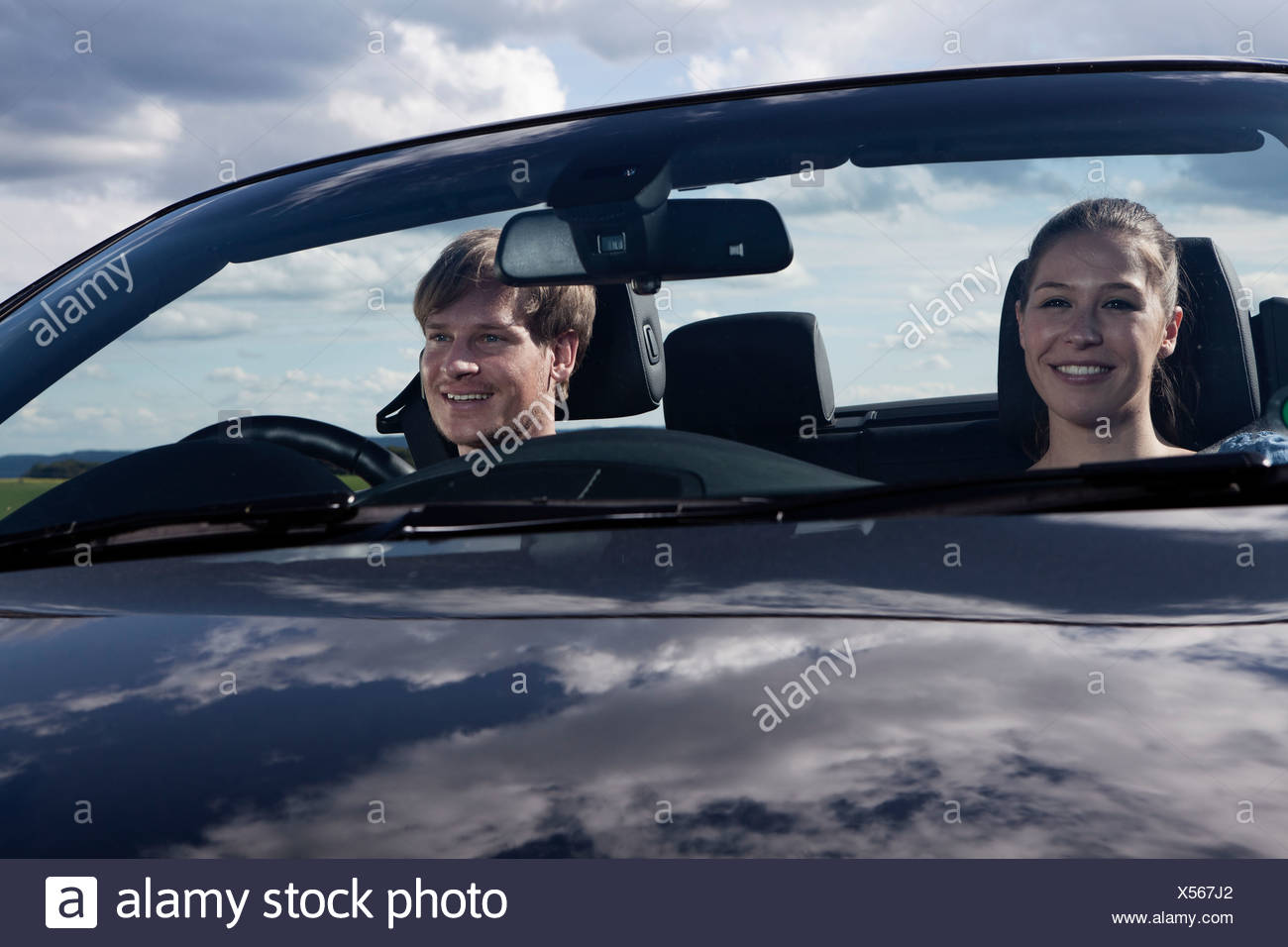 Germany, Bavaria, Couple in car, smiling - Stock Image