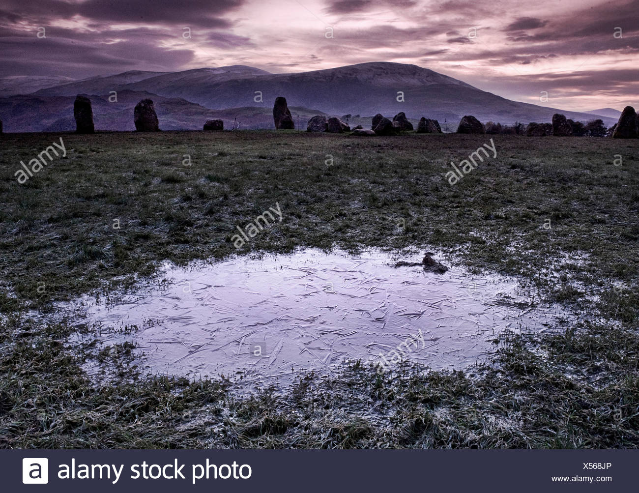 A frozen puddle in a field with nearby standing stones and mountains in the distance - Stock Image