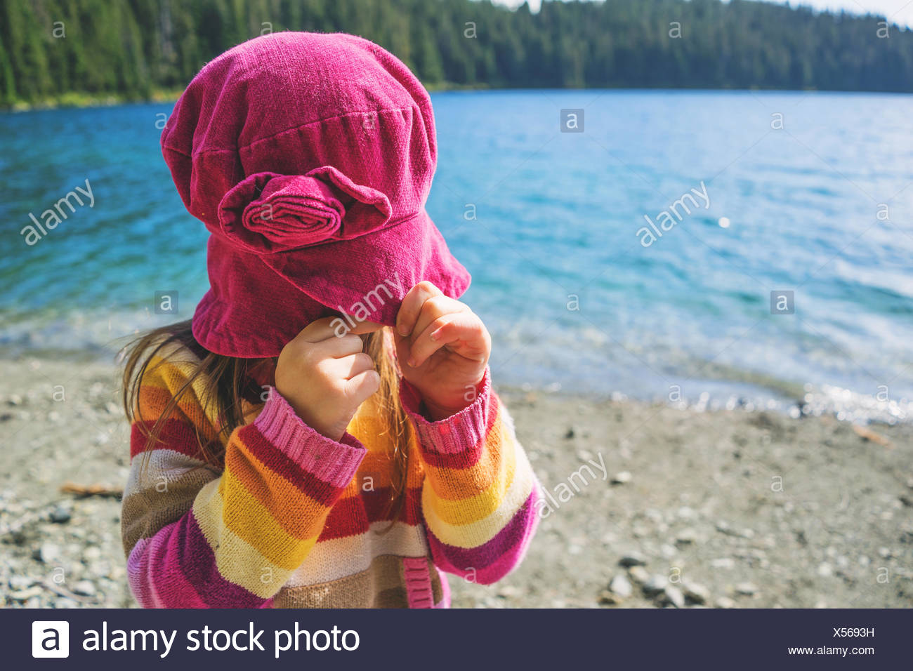Girl pulling her hat down over her face - Stock Image