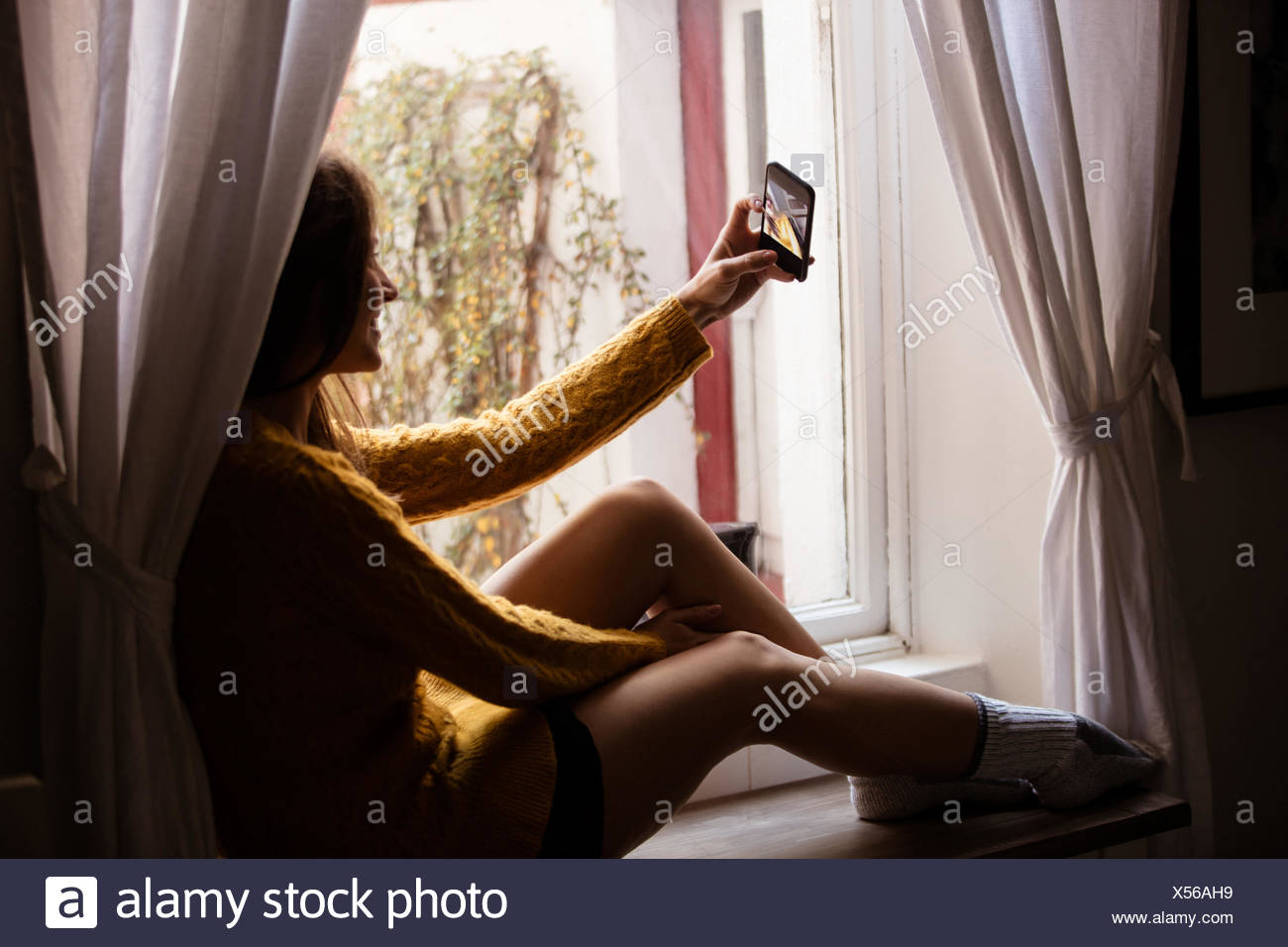 Young woman taking a selfie near the window - Stock Image