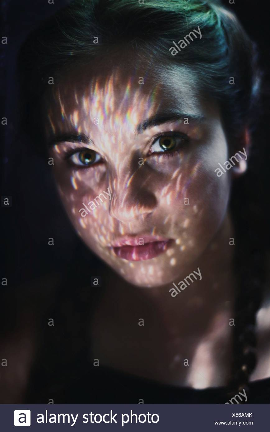 Portrait of young woman with illuminated face - Stock Image
