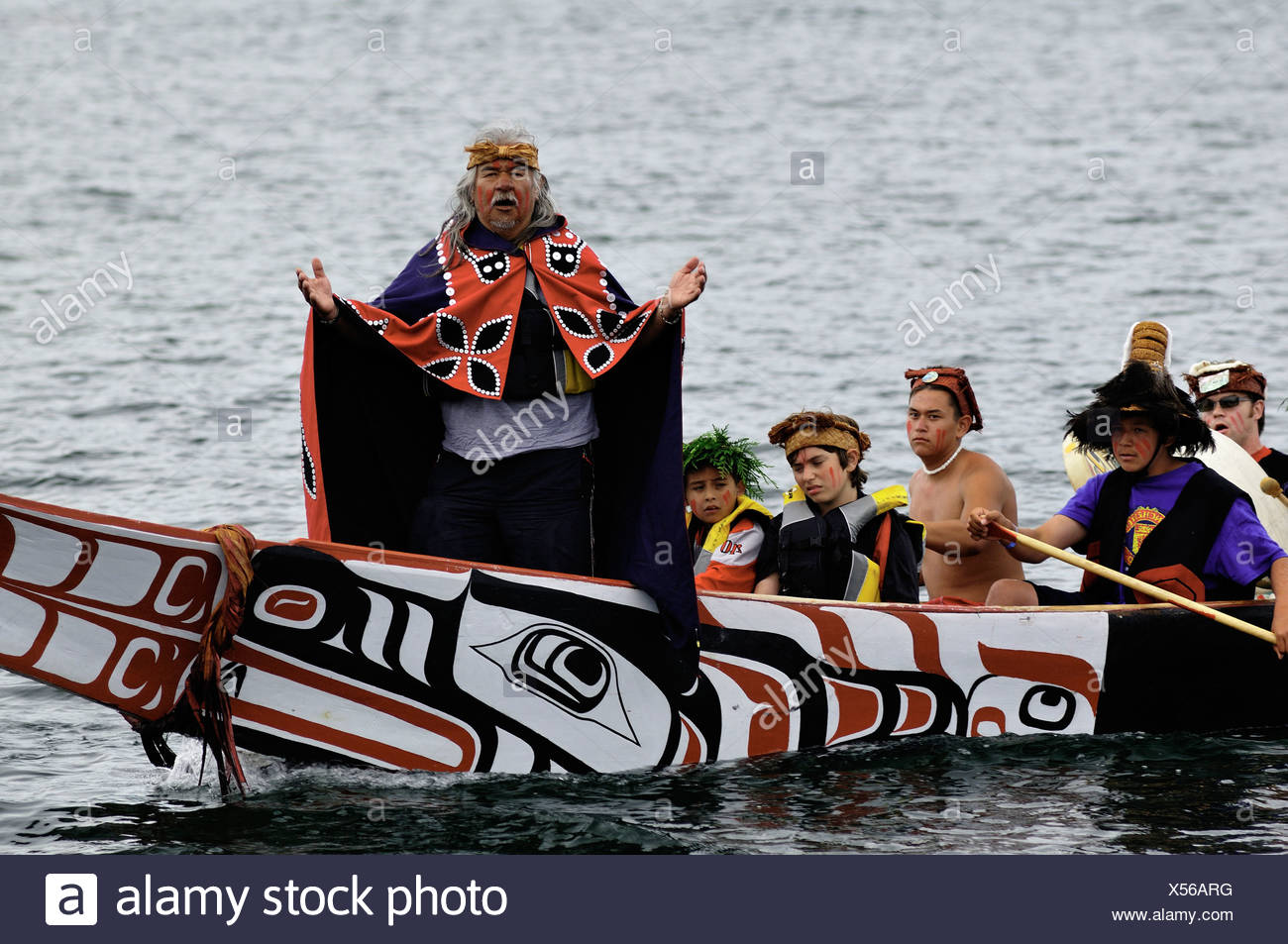 Native man standing at bow of canoe during Tribal Journeys event at the North American Indigenous Games in Duncan. - Stock Image