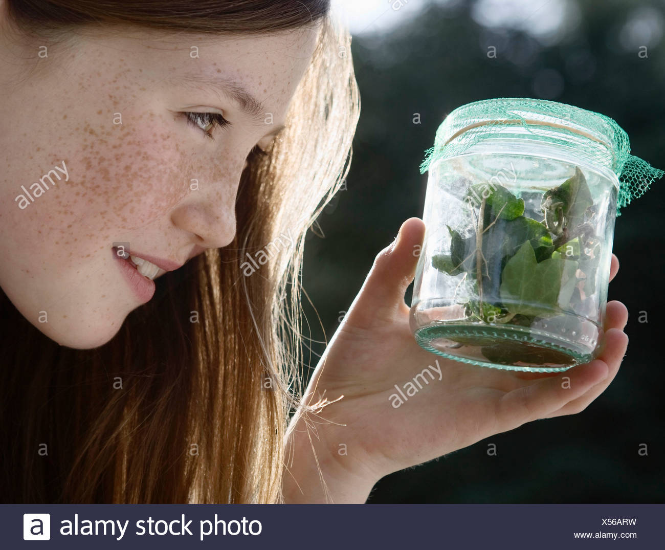 Girl holding jar of insects - Stock Image