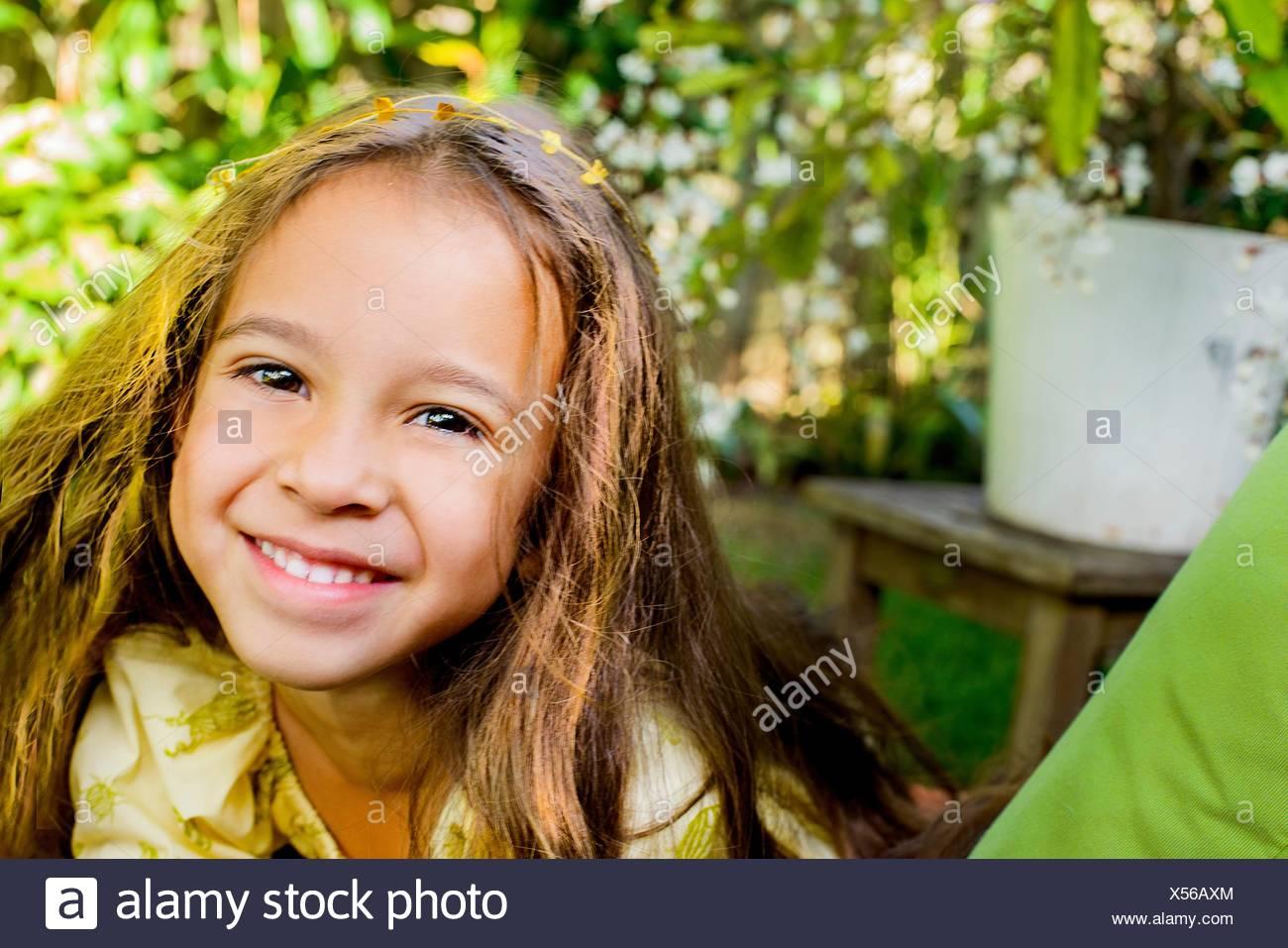 Portrait of pretty smiling girl in garden - Stock Image