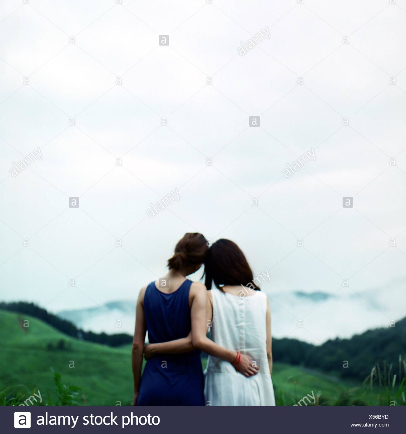 Rear View Of Female Friends Standing On Field Against Sky - Stock Image