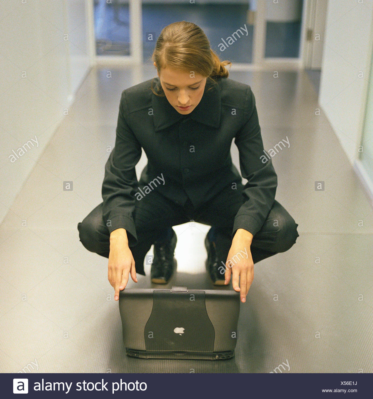 Woman crouching down in front of laptop Stock Photo