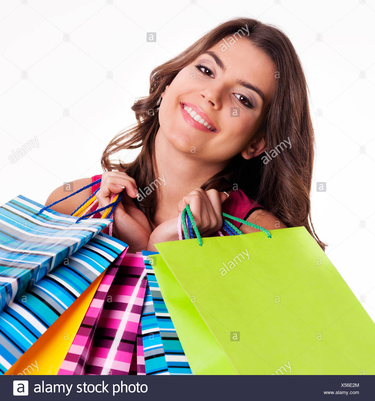 Happy woman holding multi colored shopping bags, Debica, Poland. - Stock Image