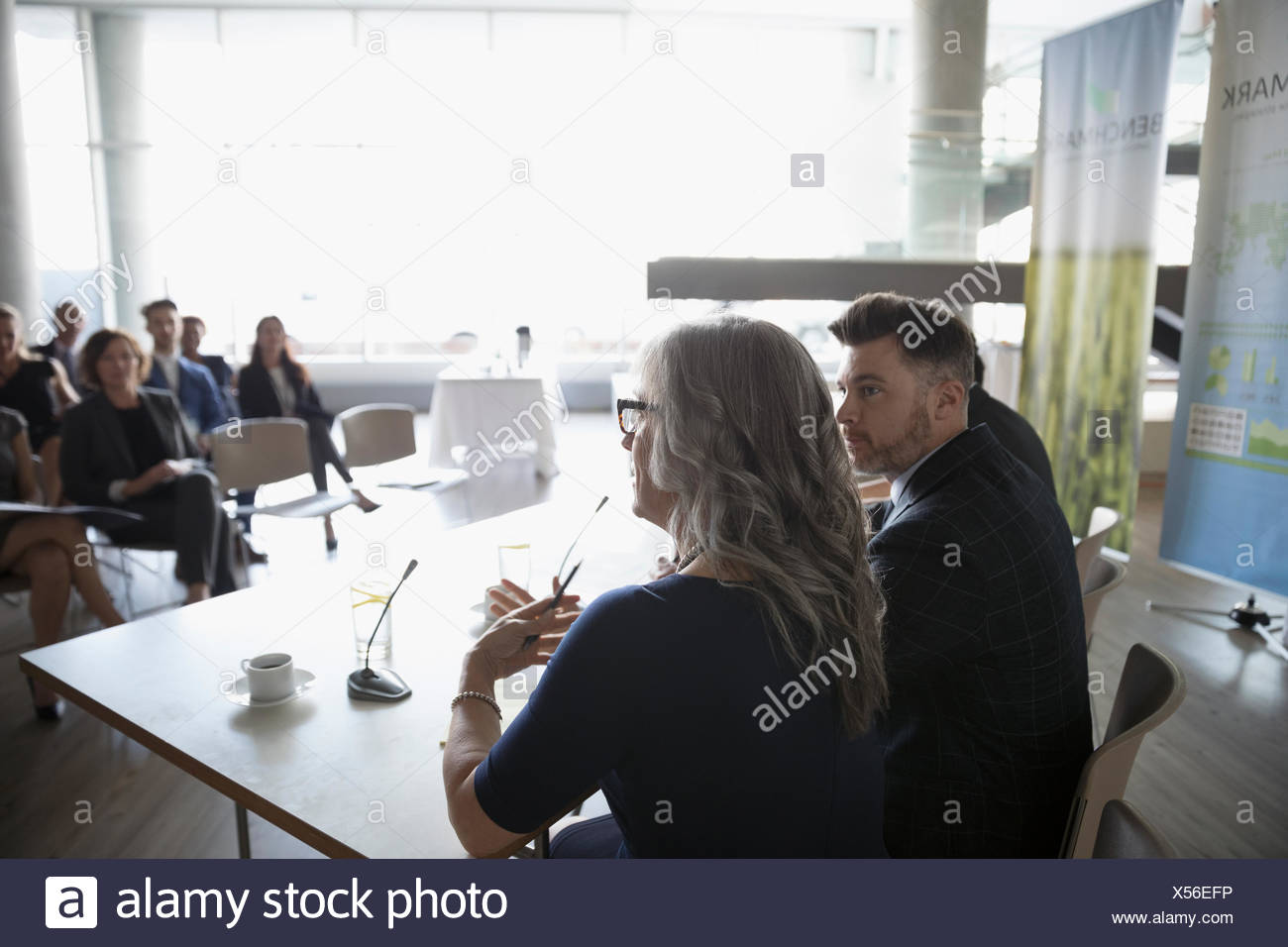 Businesswoman on conference panel talking to audience - Stock Image