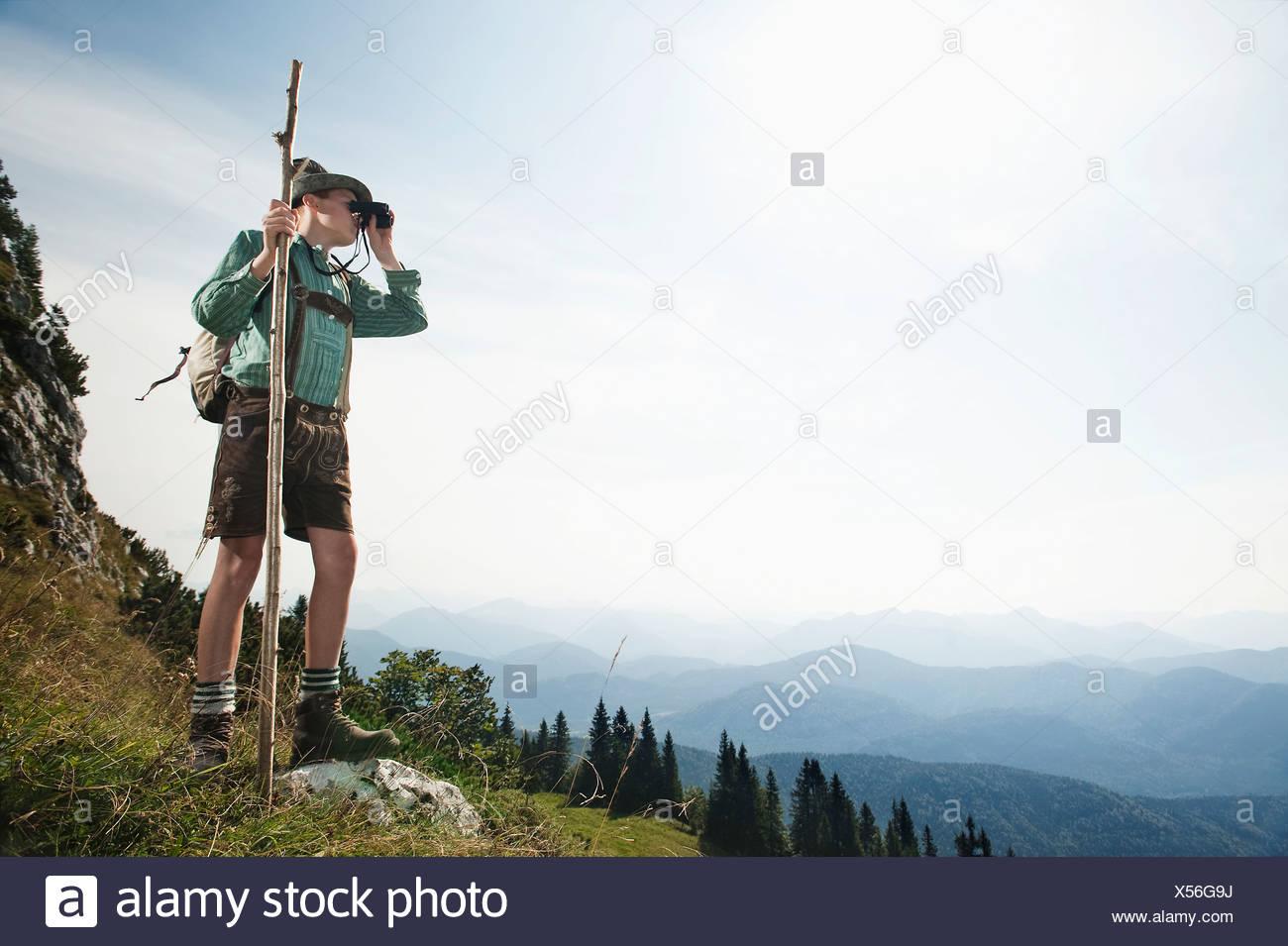 Germany, Bavaria, Boy looking through binoculars in the mountains - Stock Image