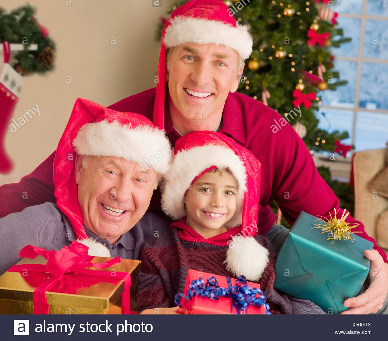 Multi Generation Family Wearing Santa Hats And Holding Christmas Gifts