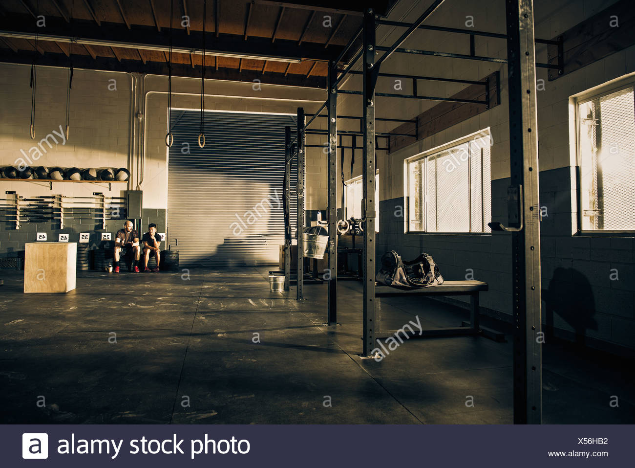 Two men taking a break from training in gymnasium - Stock Image