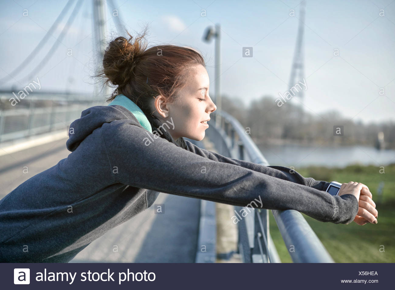 Young woman with heart rate monitor relaxing after jogging - Stock Image
