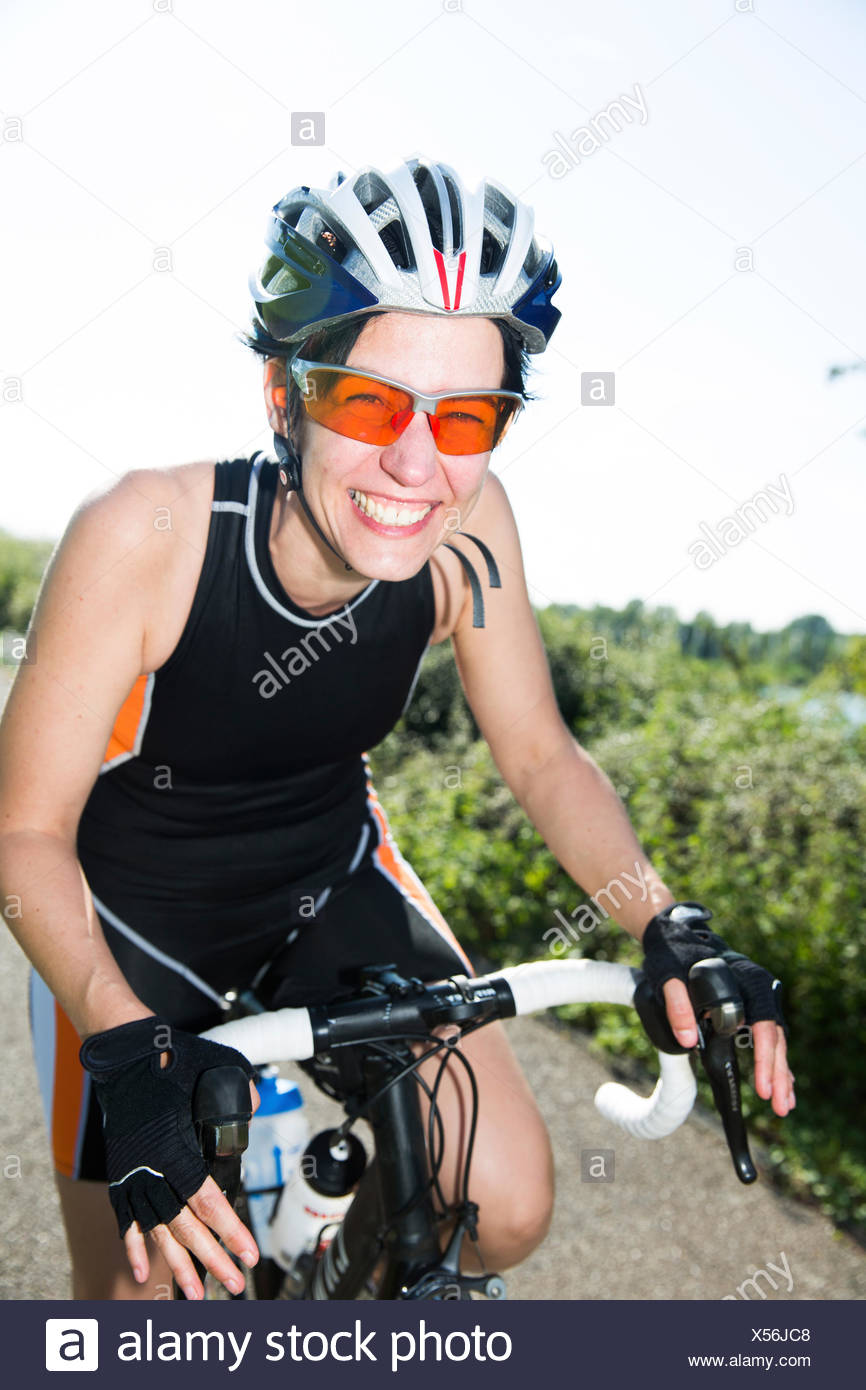 Portrait of happy racing cyclist wearing sunglasses and cycling helmet - Stock Image