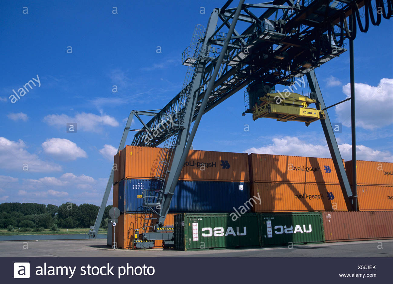 Container handling, container gantry crane moving over stacked containers - Stock Image