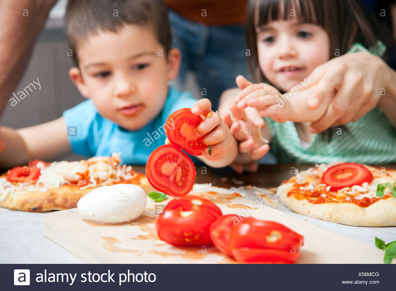 Brother and sister making homemade pizza - Stock Image